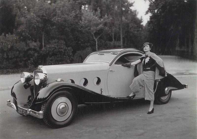 Un Delage D8 carosat în stilul epocii. Alături de acesta, o doamnă la fel de elegantă precum liniile caroseriei. Un exemplar bazat pe D8 a concurat în cadrul Concursului de Eleganță și Confort din 1934 și s-a impus în cadrul categoriei Trăsuri Închise.